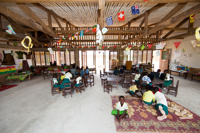 An inside view of a finished school with children in a lesson