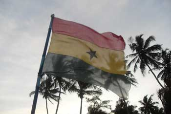 The Ghana flag flying infront of plam trees